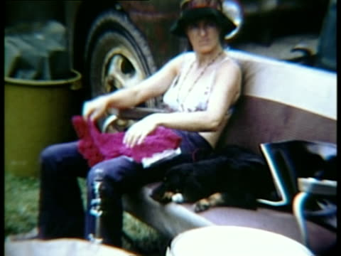 woman in bikini top and jeans sitting beside dog and folding crocheted blanket at woodstock music festival/ bethel new york usa - auf dem bauch liegen stock-videos und b-roll-filmmaterial