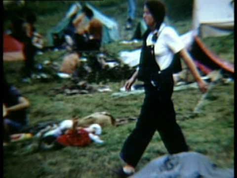 Woman in dungarees walking across grass in campsite at Woodstock music festival/ Bethel New York USA