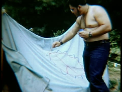 Man painting peace symbol on sheet at Woodstock music festival/ Bethel New York USA