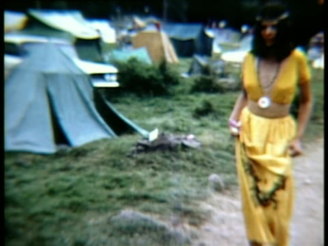 woman in long yellow skirt and top smiling at camera and walking barefoot along dirt path at woodstock music festival/ bethel new york usa - hippy stock videos & royalty-free footage