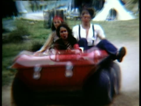vídeos y material grabado en eventos de stock de three people riding in offroad buggy on dirt path along campsite at woodstock music festival/ bethel new york usa - mujer con grupo de hombres
