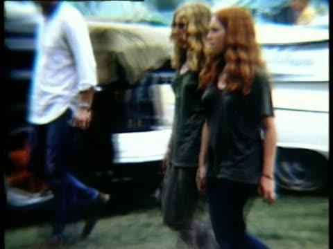 two young women walking along grass at woodstock music festival/ bethel new york usa - kiosk stock-videos und b-roll-filmmaterial