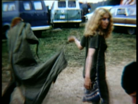 Two young women walking past on dirt path carrying sleeping bag at Woodstock music festival/ Bethel New York USA