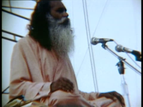 indian guru figure sitting onstage speaking and singing at the opening of woodstock music festival - 1969年点の映像素材/bロール