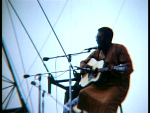 vídeos de stock e filmes b-roll de richie havens standing on stage, singing and playing guitar at woodstock music festival/ bethel, new york, usa - 1969