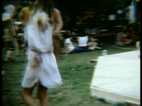 vídeos de stock e filmes b-roll de woman in white dress spinning around and dancing to music beside stage at woodstock music festival/bethel, new york, usa - 1969