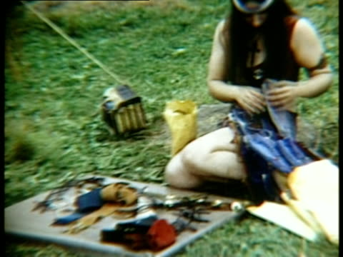 woman kneeling on grass selling goods at woodstock music festival/ bethel new york usa - 1969 stock videos & royalty-free footage