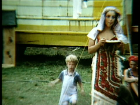 Young boy running across grass/ MS Woman wearing lace veil standing near yellow bus at Woodstock music festival/ Bethel New York USA
