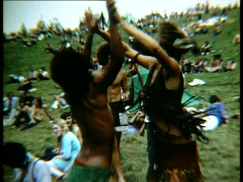 vídeos de stock e filmes b-roll de hippie couple dancing in crowd on grass at woodstock music festival, camera turning upside down/ bethel, new york, usa - jeans