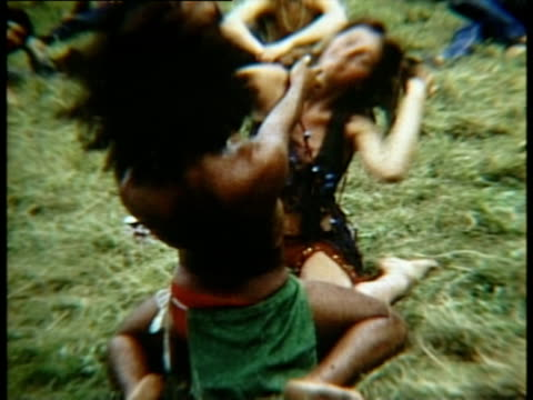 vídeos de stock e filmes b-roll de hippie couple dancing and lying down on grass at woodstock music festival/ bethel, new york, usa - 1969