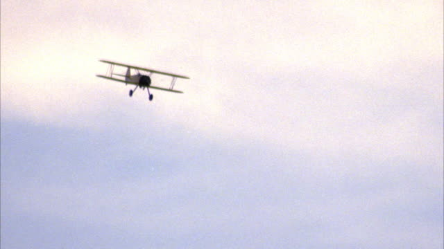 TRACKING SHOT OF YELLOW BIPLANE WITH BLUE SKY AND CLOUDS IN BACKGROUND. BIPLANE DOES LOOP AND CONTINUES.