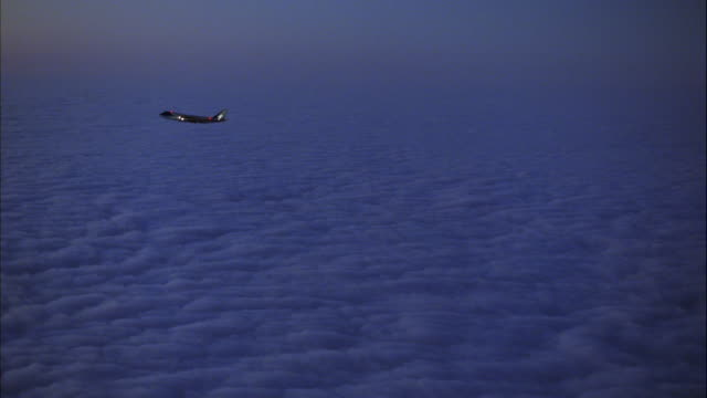 TRACKING SHOT OF AIR FORCE ONE JET FLYING ACROSS SCREEN FROM RIGHT TO LEFT ABOVE CLOUD COVER.