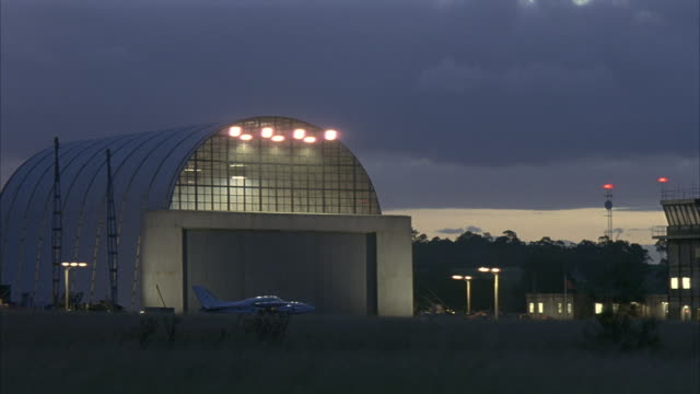 wide angle of hangar at dusk in small airport. small airplane in front of hangar. airborne object zooms across frame. could be airplane. field in foreground. - 飛行機格納庫点の映像素材/bロール