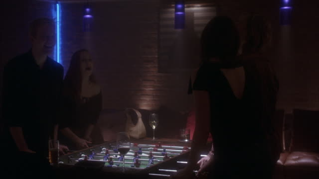 wide angle on two males and two females playing foosball in bar or pool hall. camera zooms in on drinks on both ends of foosball table. - ビリヤード点の映像素材/bロール
