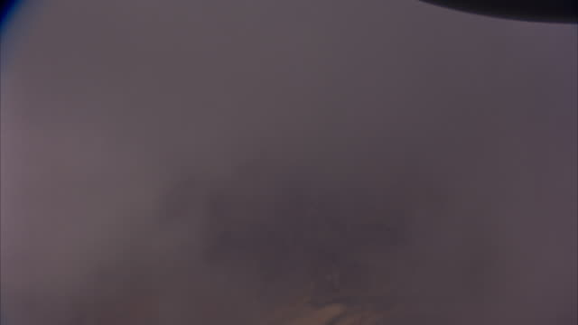 aerial of left-side window angle down from airplane or jet flying through clouds. see desert or rocky terrain below. pan up to see top of clouds and blue sky. see part of aircraft at top of frame. planes. - airplane part stock videos and b-roll footage