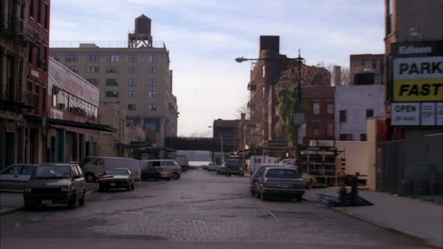 medium angle straight back moving pov of city street. see some apartment building in far right background as shot turns onto main street to right. - 1989 stock videos and b-roll footage