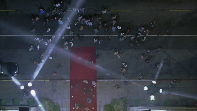 HIGH ANGLE DOWN OF RED CARPET ENTRANCE WITH SPOTLIGHTS. CROWD EXITS BUILDING COULD BE HOTEL AND FILTERS INTO STREET. POLICE CARS ARRIVE AND OFFICERS RUN INTO BUILDING.  COULD BE USED FOR MOVIE PREMIERE.