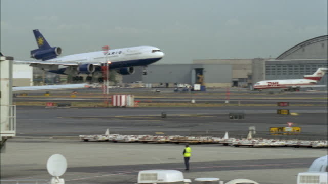 tracking shot of varig brasil airplane landing on runway at airport from left to right. see terminal at end that reads northwest and airplane on right. - luftfahrzeug stock-videos und b-roll-filmmaterial