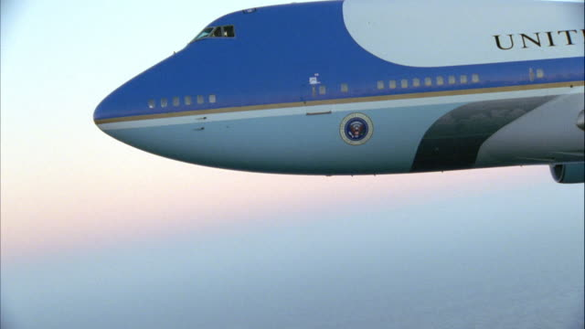 CLOSE ANGLE OF PRESIDENTIAL SEAL ON AIR FORCE ONE JET FLYING ACROSS SCREEN FROM RIGHT TO LEFT. AT END, CAMERA ZOOMS OUT TO SHOW MORE OF JET AND THEN ZOOMS BACK IN THREE TIMES.