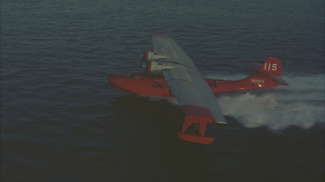 aerial of small dual propeller red airplane taking off or performing take-off in ocean or sea. see water splash underneath as water plane accelerates and begins flying. seaplanes. - propeller video stock e b–roll
