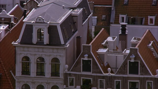 WIDE ANGLE OF EUROPEAN TOWNHOUSE NEIGHBORHOOD ROOFTOPS. LOOKS LIKE RESIDENTIAL AREA. SEE GREEN CONIFEROUS TREES THROUGHOUT.