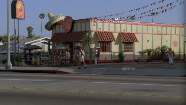medium angle of mexican fast food restaurant. patrons sitting in gated outside area. see giant sombrero on roof. see delivery truck start to pull out of restaurant parking lot. - 1989 stock videos and b-roll footage