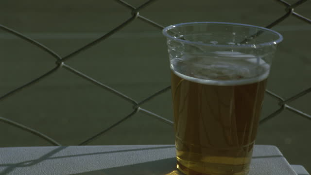 close angle of plastic cup of beer on top of cooler with chain link fence in background. cooler and beer begin to shake as race cars pass by on racetrack in background. alcohol. - fence stock-videos und b-roll-filmmaterial