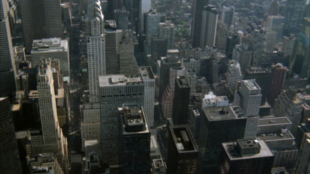 vídeos de stock, filmes e b-roll de high-level aerial of new york city skyline mostly of building rooftops. shot moves slowly northwest bound and towards the end shows pan am building on the bottom left corner. chrysler building. skyscrapers. - 1980 1989