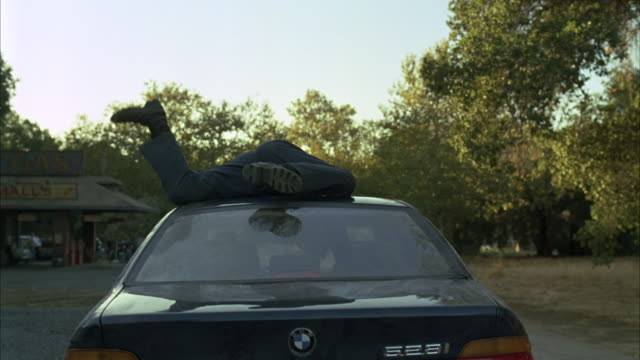 wide angle of car driving with man's legs sticking out of sunroof. camera follows close behind blue bmw 528i as it drives down rural one lane road past gas station. car swerves off road. stunts. rural areas. - bmw stock videos & royalty-free footage
