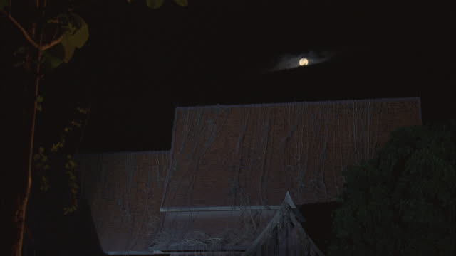 wide angle of full moon hidden by clouds above house. could be farmhouse with steep roof. - farmhouse stock videos & royalty-free footage