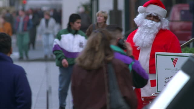 medium angle of man dressed in santa claus costume ringing bell and trying to solicit donations. see some people give donations and others pose to take pictures with santa. - pavement stock videos & royalty-free footage