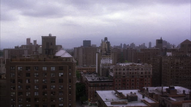 PAN LEFT TO RIGHT, WIDE ANGLE SHOT, POV FROM UPPER STORY OR ROOF OF NEW YORK BUILDING LOOKING OUT OVER RESIDENTIAL SECTION OF CITY. CAMERA PANS LEFT TO RIGHT OVER  RUN DOWN OR ABANDONED EARLY 20TH CENTURY BRICK APARTMENT