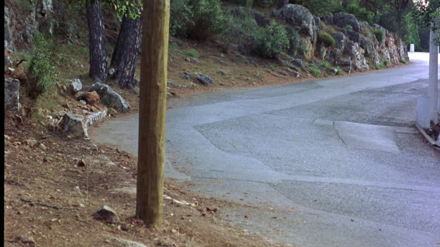 WIDE ANGLE OF CITROEN DS 21 CAR BEING CHASED BY 1985 BMW 520I SEDAN ON WINDING COUNTRY OR MOUNTAIN ROAD. CARS SWERVE ONTO DIRT ROAD WHEN RENAULT KANGOO APPROACHES IN ONCOMING DIRECTION. CAR CHASES.