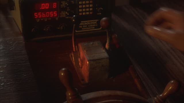 close angle of ship's bridge, control room. see top of wooden steering wheel and two levers above. digital readout on machine with buttons. man's hand, arm in raincoat works to push levers forward. - control stock videos and b-roll footage