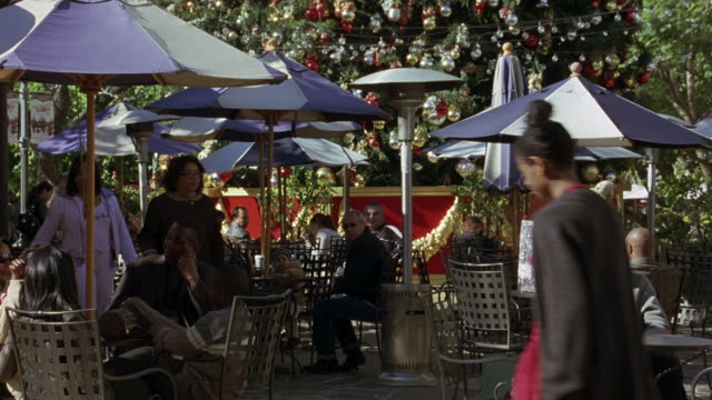 hand held angle of a large christmas tree in a shopping center to a collection of umbrellas, tables, and chairs. cafe called surf city.  the shoppers hold bags filled with their christmas shopping. - the grove los angeles stock videos & royalty-free footage