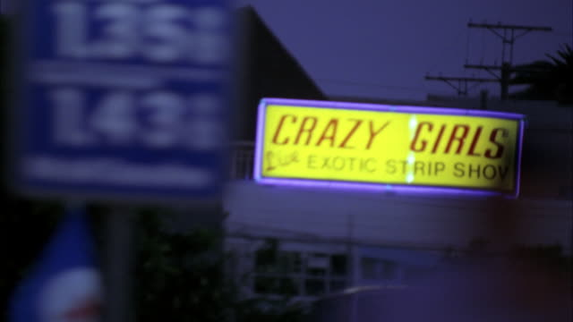 vidéos et rushes de wide angle, moving pov from right side of car.  sign on strip club reading crazy girls - live exotic strip show. - peep show