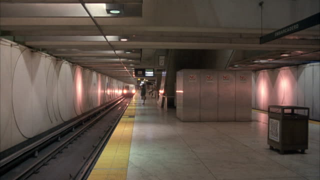 vídeos y material grabado en eventos de stock de wide angle of bart subway station with train tracks on left. people waiting on platform. subway train appears from distance and stops. signs on train read bart and ba. the embarcadero bart station, san francisco. - bart