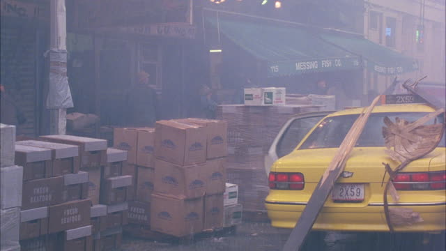 MEDIUM ANGLE OF TAXICAB PULLED UP ALONGSIDE STACKS OF BOXES IN FRONT OF STORES. SEE TWO PEOPLE SUDDENLY FLEE FROM BACK OF TAXI. THEN SEE ANOTHER TAXI CRAZILY DRIVE DOWN SIDEWALK CRASHING THROUGH BOXES. SEE OTHER PEOPLE RUNNING AWAY.