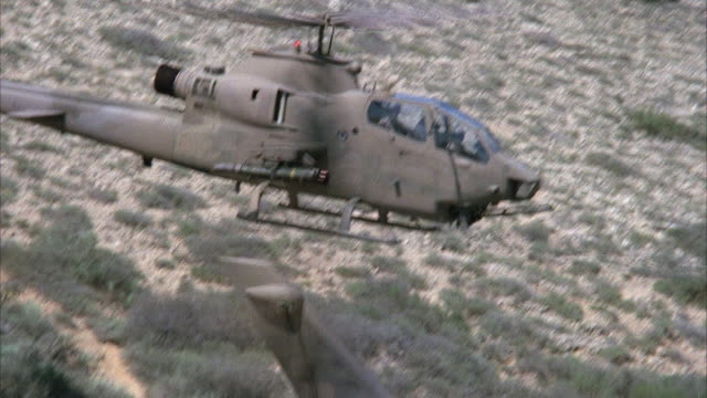 MEDIUM ANGLE OF COBRA MILITARY HELICOPTER FLYING IN PLACE CLOSE TO GROUND ARID AREA OR DESERT WITH SHRUBS IN BACKGROUND. MIDDLE EAST. ATTACK HELICOPTERS.