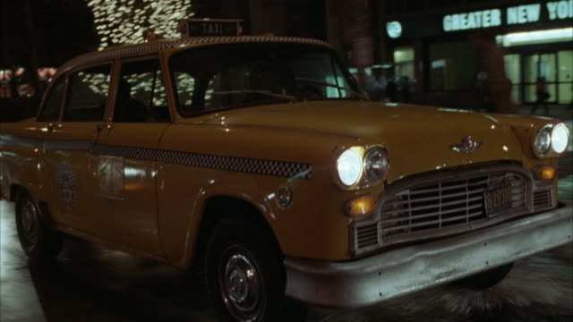 tracking shot moving pov of yellow taxi driving along city street, could be rear angled process plate. pass building that reads greater new york savings bank. - yellow taxi bildbanksvideor och videomaterial från bakom kulisserna