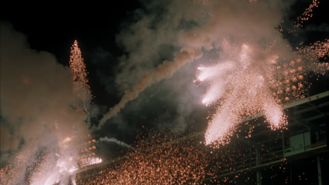 vídeos de stock e filmes b-roll de medium up angle of fireworks exploding through stadium lights. see smoke and sparks from fireworks. see two sets of stadium lights on top of stadium. explosions. - estádio