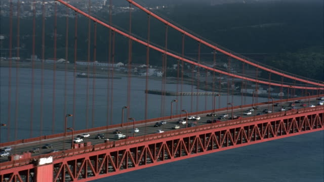 vídeos y material grabado en eventos de stock de pull back of golden gate bridge, pov on marin side of bridge. starts with medium angle of cars driving on bridge and pulls back to wider angle of bridge. san francisco skyline in far background. see bay below. - 1993
