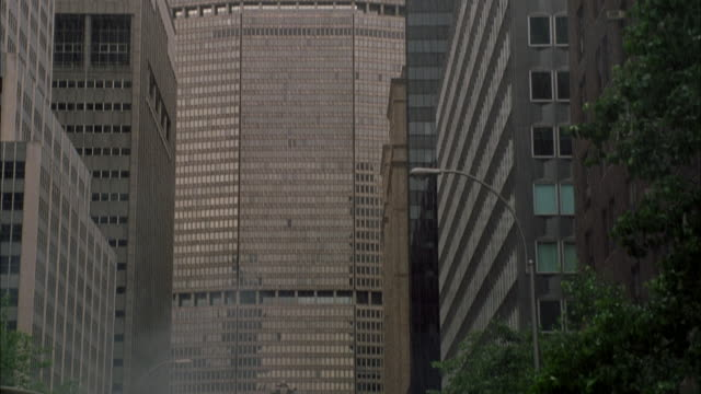 stockvideo's en b-roll-footage met pan down from top of metlife office building to soldiers running down middle of street below. soldiers are looking up to top of building. also see several soldiers run past foreground. see rain pouring down. - metlife building