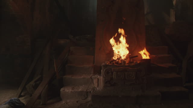 stockvideo's en b-roll-footage met wide angle of stone basement chamber with large stone idol or altar, carvings. small fire flames burning at base of figure. camera pov  pans, moves away from altar. - altaar