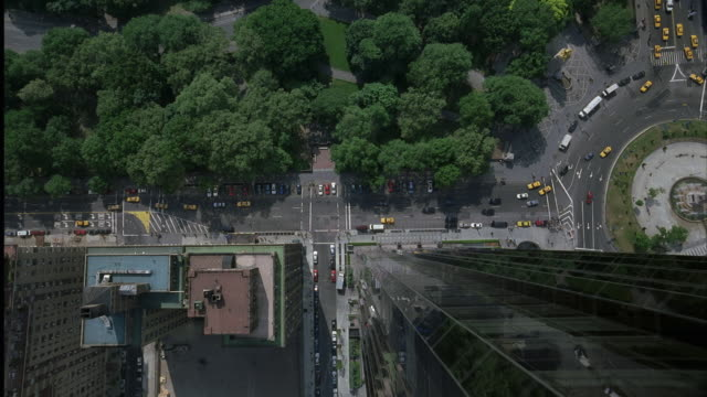 aerial birdseye pov. camera looking out over central park and manhattan. camera mounted on track. camera pulls forward over edge of high rise. looking straight down at city street. camera falls down side of building then pans up. - anno 2001 video stock e b–roll