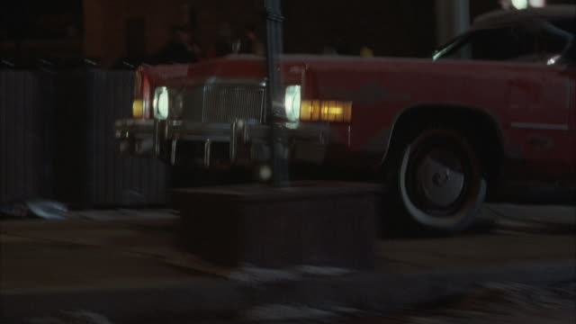 vídeos de stock, filmes e b-roll de tracking shot of 1974 red cadillac eldorado driving from right to left on sidewalk behind parked cars. car drives onto street at end, then exits left. see bottom of car during shot. - cadillac