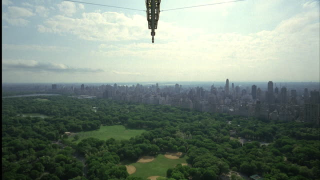 aerial, pan down. opens with wide angle shot of central park from top of high rise. camera mounted on track. camera runs along track to edge of building. pans down and falls down side of building. - anno 2001 video stock e b–roll