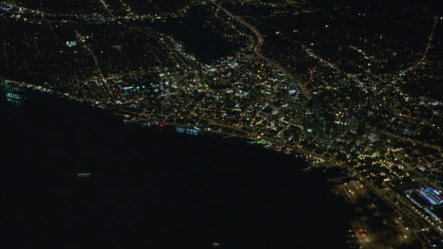 AERIAL OF SEATTLE AT NIGHT SURROUNDED BY PUGET SOUND COASTLINE. SEE DOWNTOWN AREA AND TWO BOATS IN WATER. CAMERA FLIES DOWN LEVEL OF BUILDING TOPS. SEE TRAIN AND CARS.