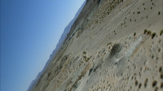 AERIAL OF ISOLATED DESERT AREA WITH MOUNTAIN SPIRES. FLYING POV. SEE SUN AND SUN HALATIONS.