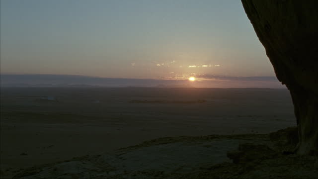 MEDIUM ANGLE OF SUNRISE FROM DESERT HORIZON. SEE SUN PARTLY  BEHIND CLOUDS. SEE CLOUDS MOVE IN THE DISTANCE. SEE OUTLINE OF DARK CLOUDS AND MOUNTAINS IN BACKGROUND.
